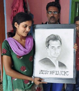 Family of Mohammed Shami hold his portrait